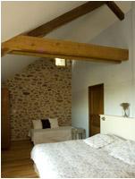 Chambre mansardée avec mur en pierre