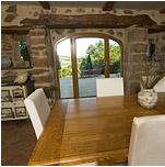 Salle à manger avec vue sur la cours principale au travers d'un porche en pierre